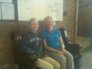 Julia and her mom posing on the pew in the barn aisle before heading out to a horse show