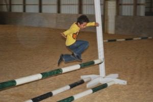 Salman jumps while playing games in the shady indoor arena after his riding lesson - Clairvaux Summer Horse Camp