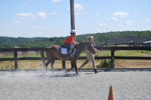 Spencer learns two-point position while Eliza lends a hand - Clairvaux Summer Horse Camp